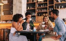 一起享用咖啡的不同的小组朋友 库存图片