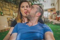 一起享用在后院的年轻夫妇 他们是一起微笑,笑和做滑稽的面孔 免版税库存图片