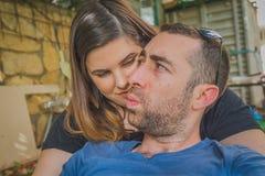 一起享用在后院的年轻夫妇 他们是一起微笑,笑和做滑稽的面孔 图库摄影