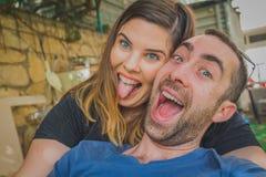 一起享用在后院的年轻夫妇 他们是一起微笑,笑和做滑稽的面孔 库存照片