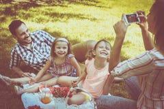 一起享用在野餐的愉快的家庭 家庭在草甸 飞蛾 免版税库存照片