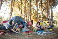 一起享用在露营地的年轻朋友 免版税库存图片