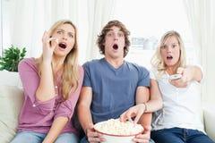 一起享用玉米花的三个朋友,当冲击在电视时 免版税库存照片