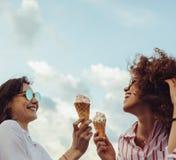 一起享用的朋友用冰淇凌 免版税库存图片