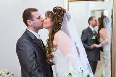 一起亲吻年轻婚礼的夫妇 免版税库存照片