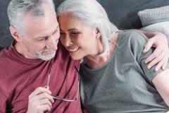 一起休息在床上的愉快的夫妇在家 免版税库存图片