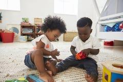 一起使用与在游戏室的玩具的男婴和女孩 免版税库存图片