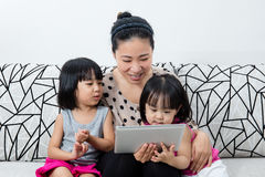 一起使用与数字式片剂的愉快的亚洲中国家庭 图库摄影