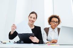 一起使用剪贴板和膝上型计算机的两名愉快的女实业家 免版税库存照片