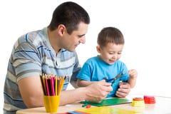 一起使用和切开纸的父亲和儿子 库存照片