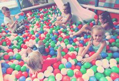 一起使用在与塑料多彩多姿的球的水池的孩子 免版税库存图片