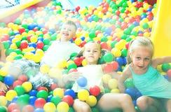 一起使用在与塑料多彩多姿的球的水池的孩子 库存图片