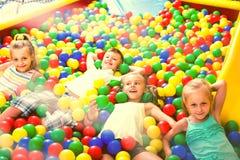 一起使用在与塑料多彩多姿的球的水池的孩子 库存照片