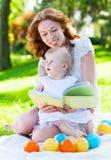 一起使用在公园的秀丽妈咪和她的孩子 库存照片