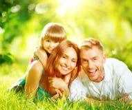 一起使用在夏天公园的年轻家庭 免版税库存照片
