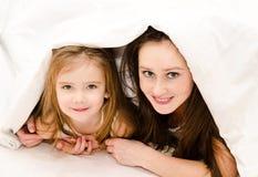 一起使用在床上的微笑的母亲和她的小女孩 免版税库存照片