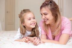 一起使用在床上的母亲和女儿 免版税库存照片