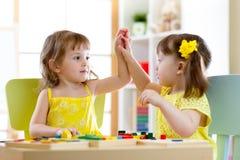 一起使用在托儿的两个逗人喜爱的小女孩 免版税库存照片