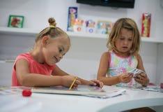 一起使用在操场的两个小女孩 免版税库存图片