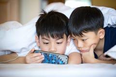一起使用在智能手机的亚裔学龄前男孩 免版税库存照片