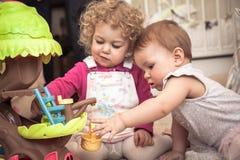 一起使用在有象征儿童通信和愉快的童年的玩具的孩子屋子里的孩子 库存图片