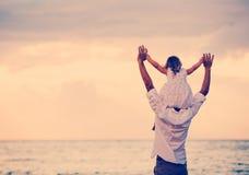 一起使用在海滩的父亲和女儿在日落 图库摄影