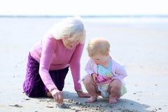 一起使用在海滩的祖母和孙女 免版税库存图片