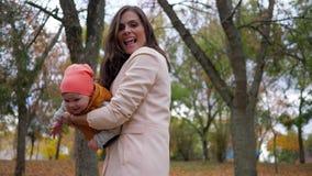 一起使用在秋天公园,家庭的妈妈和孩子获得在背景树的乐趣 影视素材