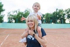 一起使用在网球场的妈妈和小女儿 免版税库存照片
