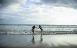 一起使用在获得日落的光的海滩的两个少妇朋友或姐妹享受暑假的乐趣在女孩绊倒 免版税库存照片