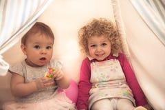 一起使用在象征儿童通信和愉快的童年的圆锥形小屋的孩子屋子里的孩子 免版税库存照片