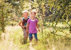一起使用在晴朗的夏天庭院里的小女孩和男孩 免版税库存照片