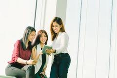 一起使用数字式片剂的三个美丽的亚裔女孩 职业妇女或聊天在有拷贝空间的办公室的大学生 库存图片