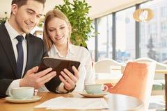 一起使用数字式片剂的企业同事 免版税库存照片