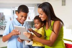 一起使用数字式片剂的母亲和孩子在厨房 库存图片