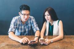 一起使用智能手机的年轻亚裔夫妇、大学生或者工友在咖啡馆,与小配件技术的现代生活方式 免版税库存照片