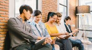 一起使用智能手机,便携式计算机,数字式片剂的不同种族的不同的小组年轻和成人人民 图库摄影