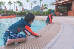 一起使用的两兄弟姐妹在水水色公园水池 免版税库存照片