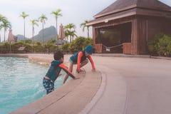 一起使用的两兄弟姐妹在水水色公园水池 库存照片