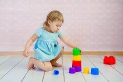 一起使用的孩子 与块的婴孩戏剧 幼儿园和幼儿园孩子的教育玩具 小女孩修造 图库摄影