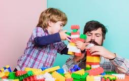 一起使用的重要性 爸爸和儿子获得乐趣 幼稚快乐的爸爸和滑稽的儿子 爸爸有孩子的戏剧玩具 ?? 免版税库存照片