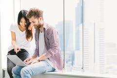 一起使用笔记本膝上型计算机的不同种族的年轻夫妇或大学生在校园或办公室 概念数字式女孩信息膝上型计算机光亮技术隧道 免版税库存图片