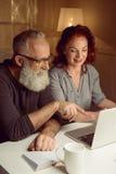 一起使用膝上型计算机的丈夫和妻子在家 库存图片