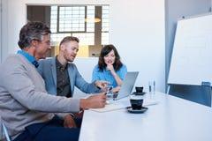 一起使用膝上型计算机的三微笑的买卖人在办公室 库存照片