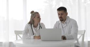 一起使用膝上型计算机的两位医生在他们的办公室和谈论患者 股票录像