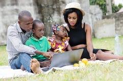 一起使用膝上型计算机的家庭在庭院 库存图片