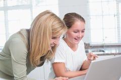 一起使用膝上型计算机的愉快的母亲和女儿 免版税库存照片
