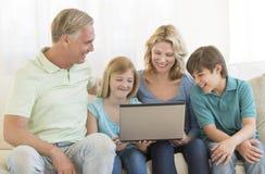 一起使用膝上型计算机的父母和孩子在沙发 免版税库存图片