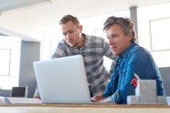 一起使用膝上型计算机的被聚焦的年轻工友在办公室 库存图片
