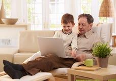一起使用计算机的祖父和孙子 库存照片